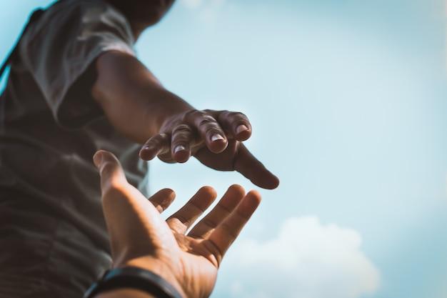 Hände strecken die hand aus, um zu helfen. Premium Fotos