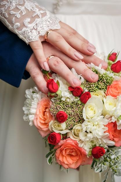 Hände und ringe auf hochzeitsblumenstrauß Premium Fotos