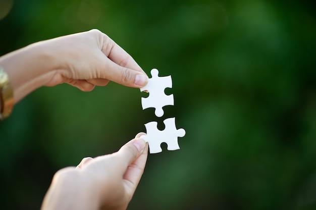 Hände und weiße puzzles nahaufnahmebild und integration geschäftskonzept und einheit Premium Fotos