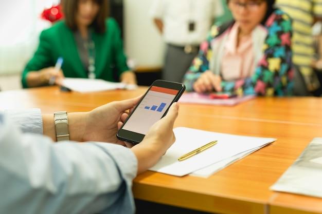 Hände unter verwendung des handys mit gelddiagramm auf lager mit gruppe geschäftsleuten. Premium Fotos