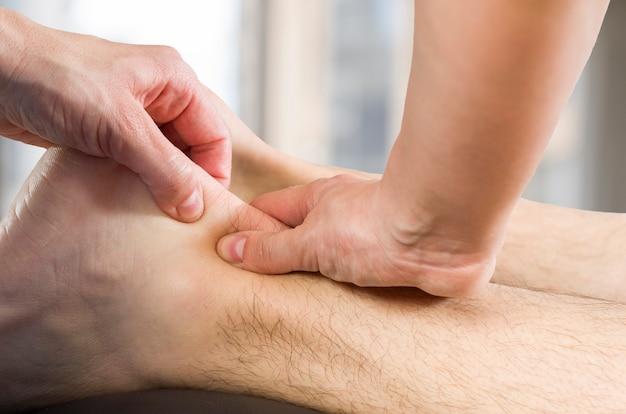 Hände von chiropraktiker, physiotherapeut, der wadenmuskelmassage tut, um patienten zu bemannen. osteopath Premium Fotos