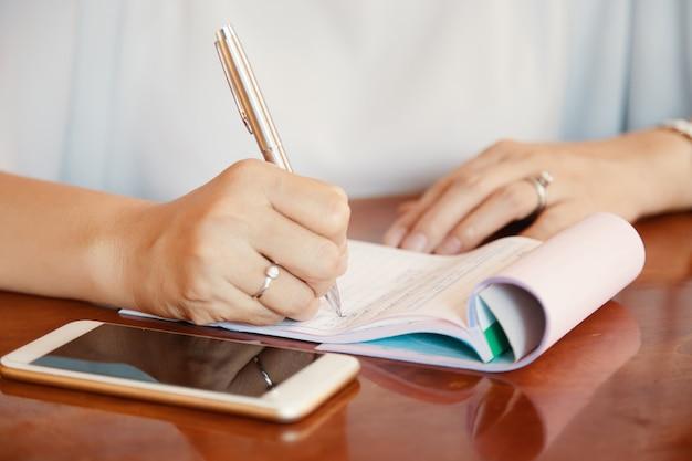 Hände von geschäftsdamenschreibensplänen und von ideasin notizblock Kostenlose Fotos