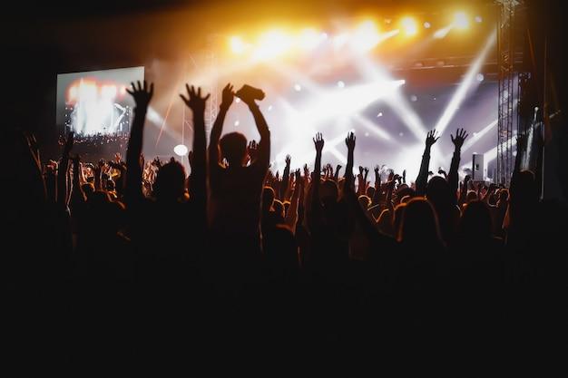 Hände von glücklichen menschen drängen sich auf der bühne beim sommer-live-rock-festival Premium Fotos