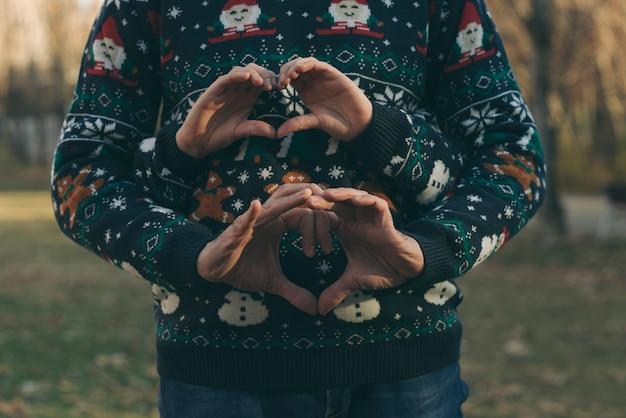 Hände von jungen und mädchen mit weihnachtskleidung Premium Fotos