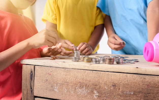 Hände von kindern helfen, münzen in sparschwein auf weiß zu setzen Premium Fotos