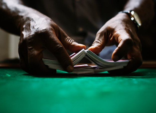 Händler, der einen kartenstapel im kasino mischt Premium Fotos