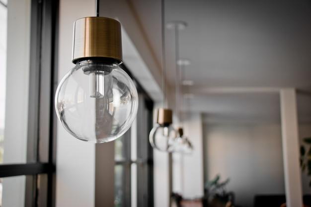 Hängende glühlampe nahe glasfenster Premium Fotos