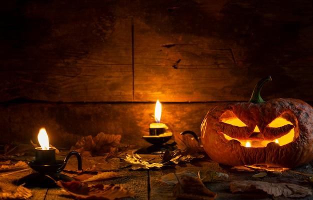 Hässliche halloween-kürbiskopfsteckfassung o-laterne auf holztisch. Premium Fotos