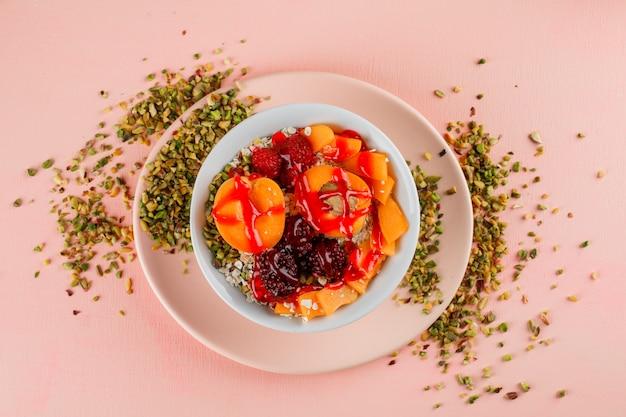 Haferflocken in einer schüssel mit pistazien, aprikosen, beeren, gelee Kostenlose Fotos