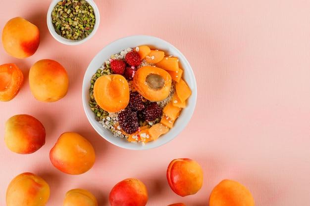 Haferflocken in einer schüssel mit pistazien, aprikosen, beeren Kostenlose Fotos