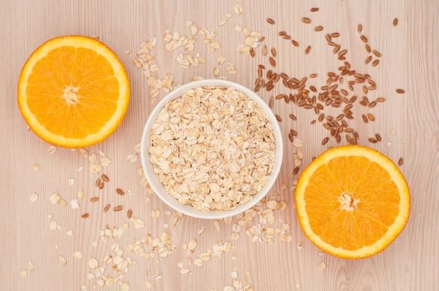 Haferflocken in einer weißen schüssel und halbierte orangen auf einem hölzernen hintergrund zum frühstück Premium Fotos