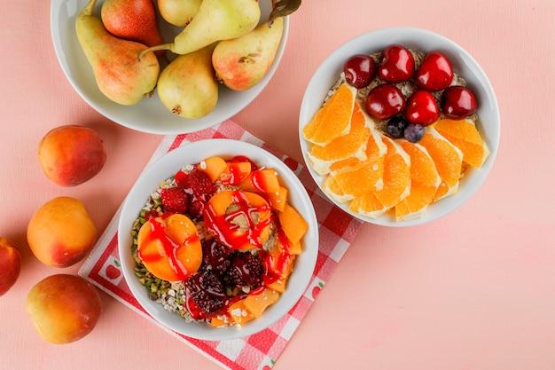 Haferflocken in schalen mit nüssen, aprikosen, beeren, birnen, kirschen, orangen Kostenlose Fotos