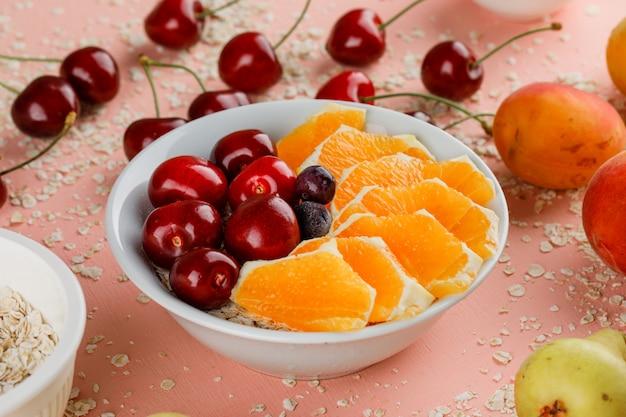 Haferflocken mit birne, aprikose, orange, kirsche, beeren in schüssel Kostenlose Fotos