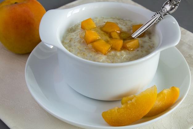 Haferflocken mit milch, aprikose und honig in der weißen platte Premium Fotos