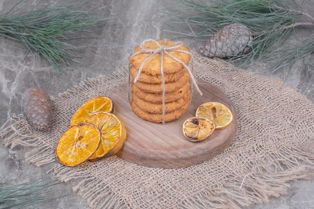 Haferkekse auf einer holzplatte mit trockenen orangenscheiben herum Kostenlose Fotos