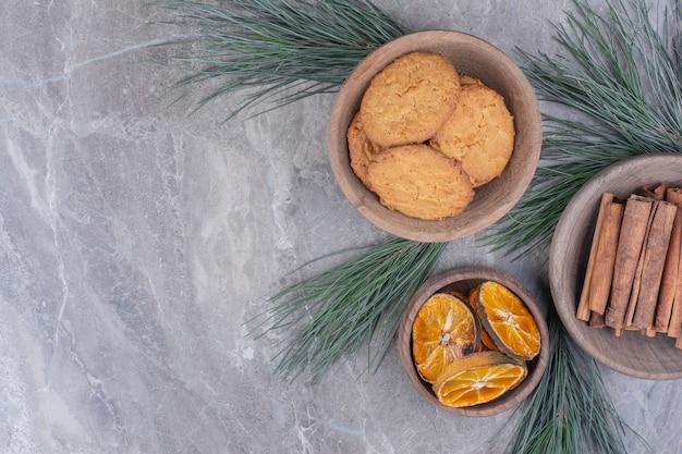 Haferkekse auf einer holztasse mit zimt und orangenscheiben Kostenlose Fotos