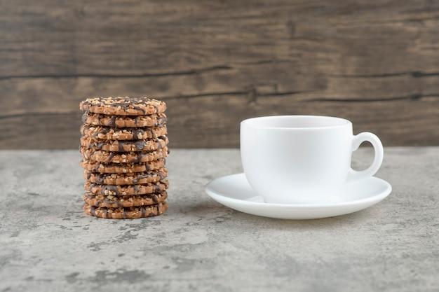 Haferkekse mit schokoladensirup mit einer tasse tee auf einem steintisch. Kostenlose Fotos