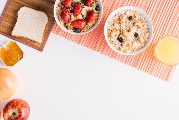 Hafermehl in der schüssel mit toast und stau auf weißer tabelle Kostenlose Fotos