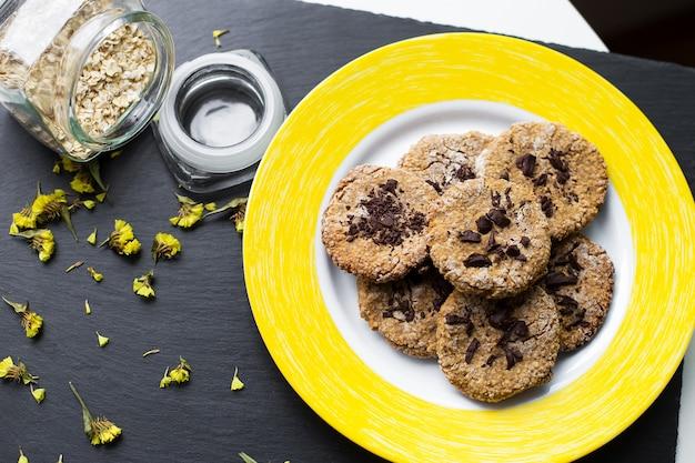 Hafermehlplätzchen mit schokolade auf gelber platte Premium Fotos