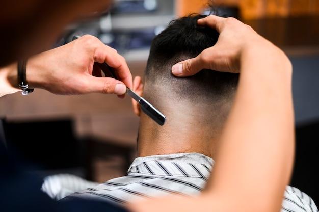 Hairstylist der hinteren ansicht, der das haar des kunden rasiert Kostenlose Fotos