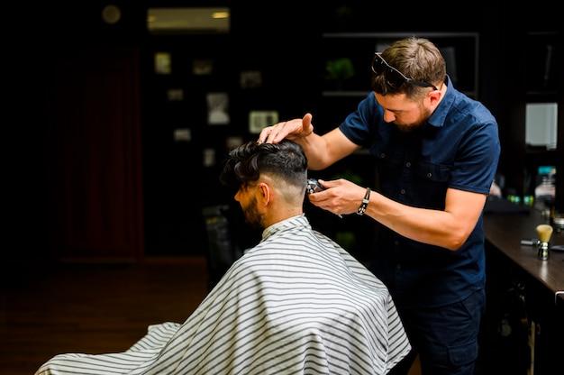 Hairstylist der hinteren ansicht, der das haar des kunden schneidet Kostenlose Fotos