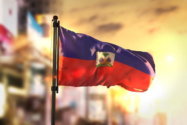 Haiti-flagge gegen stadt verschwommen hintergrund bei sonnenaufgang hintergrundbeleuchtung Premium Fotos