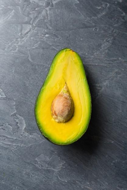 Halbe avocado auf dunklem hintergrund. biolebensmittelkonzept. Premium Fotos