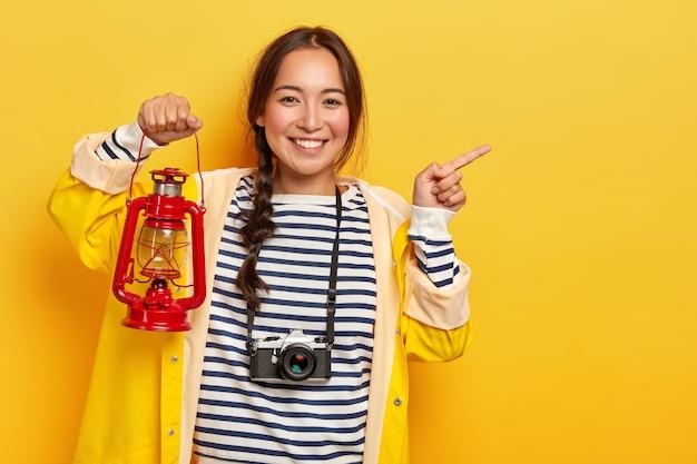 Halbe länge aufnahme von lächelnden koreanischen touristin zeigt mit dem zeigefinger weg, hält gaslampe, trägt retro-kamera am hals, lässig gekleidet, lächelt angenehm, isoiert über gelbem hintergrund Kostenlose Fotos