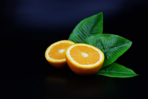 Halbe reife orange frucht nützlich mit blatt auf einem lokalisierten schwarzen hintergrund Premium Fotos