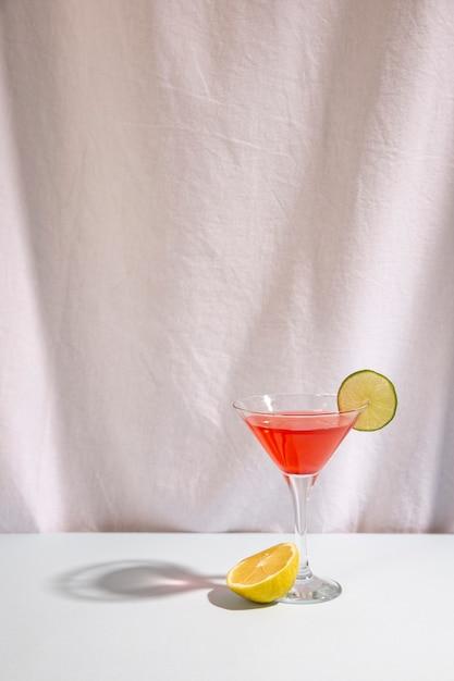 Halber kalk mit cocktailgetränk schmücken mit cocktail auf schreibtisch gegen lokalisiert auf weißem hintergrund Kostenlose Fotos