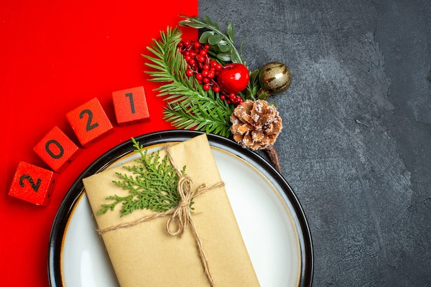 Halber schuss des neujahrshintergrunds mit geschenk auf tellerdekorationszubehör tannenzweigen und zahlen auf einer roten serviette auf einem schwarzen tisch Kostenlose Fotos