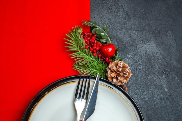 Halber schuss des weihnachtshintergrundes mit besteck, gesetzt mit rotem band auf einem teller tellerdekoration zubehör tannenzweige auf einer roten serviette auf einem dunklen tisch Kostenlose Fotos