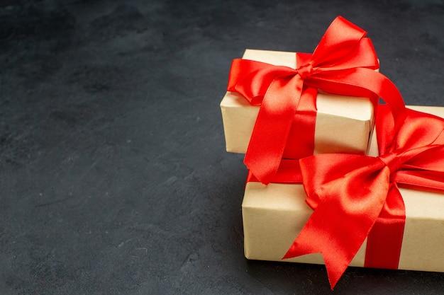 Halber schuss von schönen geschenken mit rotem band auf dunklem hintergrund in horizontaler ansicht Kostenlose Fotos