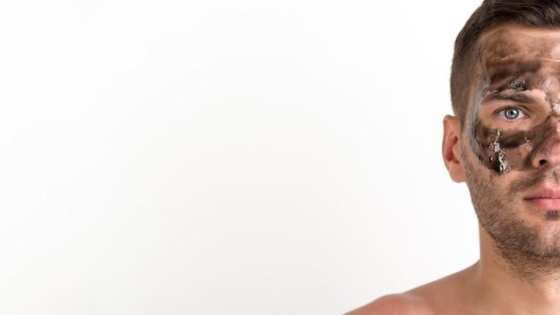 Halbes gesicht des hemdlosen jungen mannes wendete schwarze maske auf seinem gesicht gegen weißen hintergrund an Kostenlose Fotos