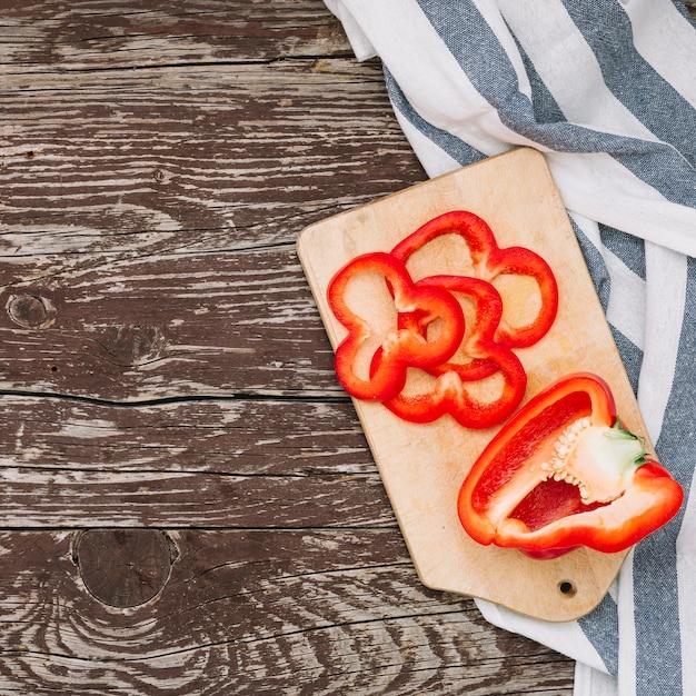 Halbiert und scheibe des roten paprikas auf hackendem brett über dem holztisch Kostenlose Fotos
