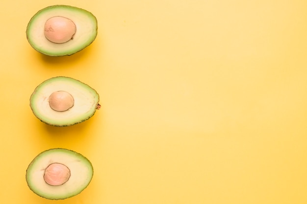 Halbierte avocado auf gelbem hintergrund Kostenlose Fotos