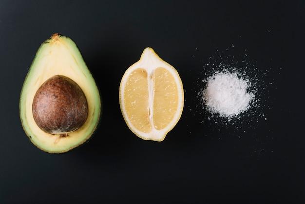 Halbierte avocado und zitrone nahe salz auf schwarzer oberfläche Kostenlose Fotos