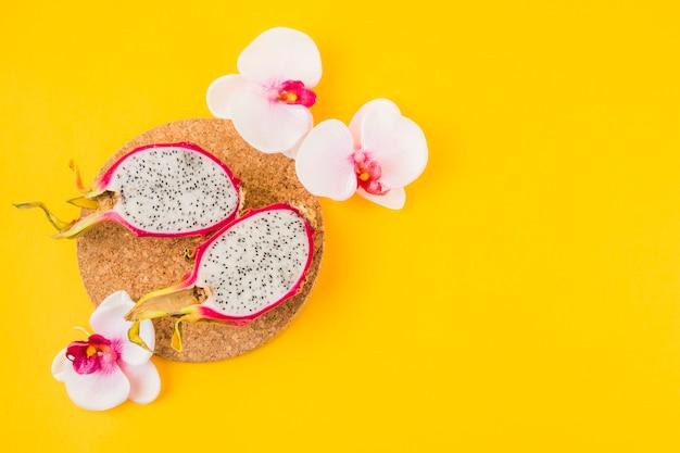 Halbierte drachefrucht auf korkenuntersetzer mit rosa orchideenblume auf gelbem hintergrund Kostenlose Fotos