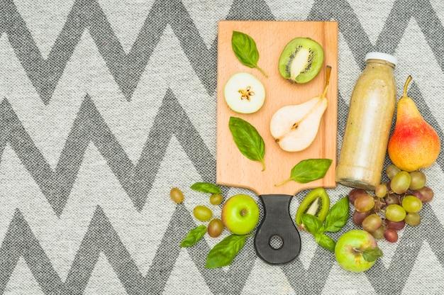 Halbierte früchte und smoothieflasche auf zickzacktextilmustertischdecke Kostenlose Fotos