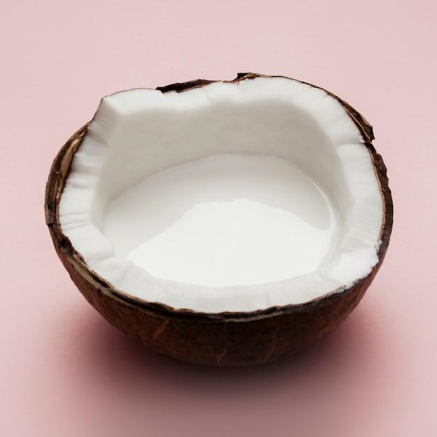 Halbierte kokosnuss auf rosa hintergrund Kostenlose Fotos