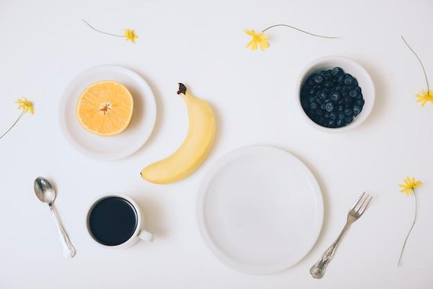 Halbierte orange; banane; blaubeerschale; kaffeetasse und eine leere platte auf weißem hintergrund Kostenlose Fotos
