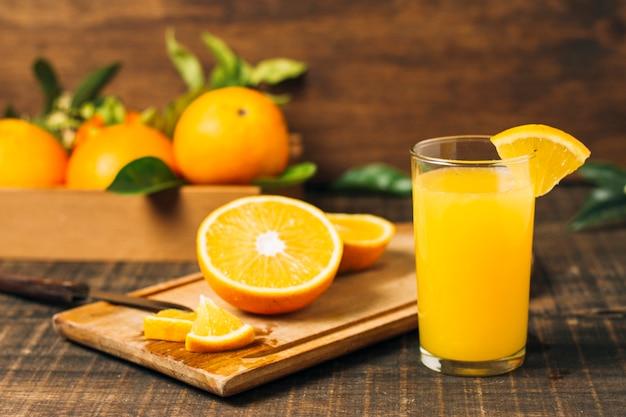 Halbierte orange der vorderansicht nahe bei orangensaft Kostenlose Fotos