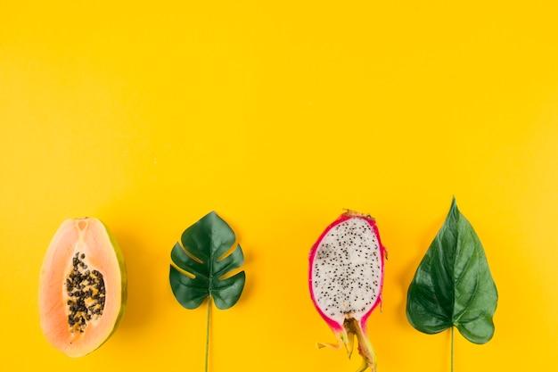 Halbierte papaya- und drachefrucht mit künstlichen blättern auf gelbem hintergrund Kostenlose Fotos