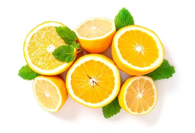 Halbierte zitronen und orangen liegen in einer reihe, draufsicht. zitrusfrüchte und minzblätter für die herstellung von limonade, kopierraum. Premium Fotos