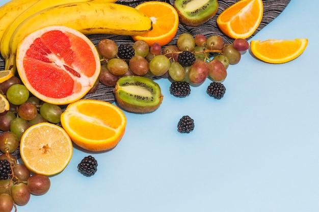 Halbierte zitrusfrüchte; trauben; banane; kiwi auf blauem hintergrund Kostenlose Fotos