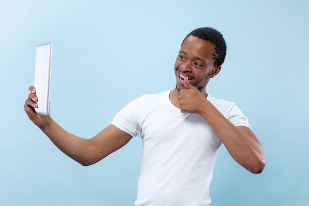 Halblanges nahaufnahmeporträt des jungen afroamerikanermannes im weißen hemd auf blauem hintergrund. menschliche emotionen, gesichtsausdruck, werbung, verkauf, konzept. verwenden des tablets für selfie, vlog, sprechen. Kostenlose Fotos