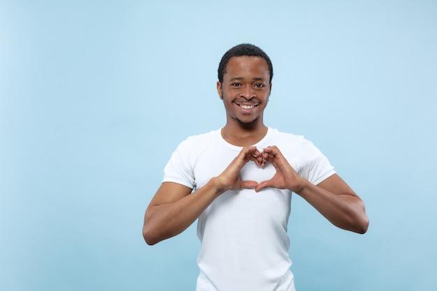 Halblanges nahaufnahmeporträt des jungen afroamerikaners im weißen hemd auf blauer wand. menschliche emotionen, gesichtsausdruck, anzeigenkonzept. er zeigte das zeichen eines herzens an seinen händen und lächelte. Kostenlose Fotos
