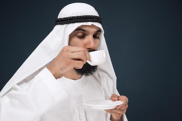 Halblanges porträt des arabischen saudischen geschäftsmannes auf dunkelblau Kostenlose Fotos
