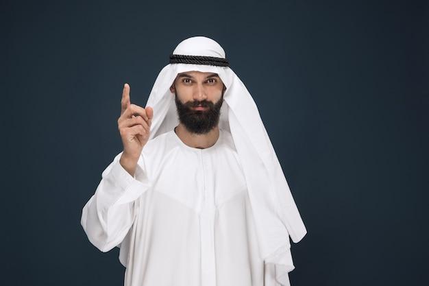 Halblanges porträt des arabischen saudischen geschäftsmannes auf dunkelblauer wand. junges männliches modell lächelnd und zeigend. konzept von geschäft, finanzen, gesichtsausdruck, menschlichen emotionen. Kostenlose Fotos