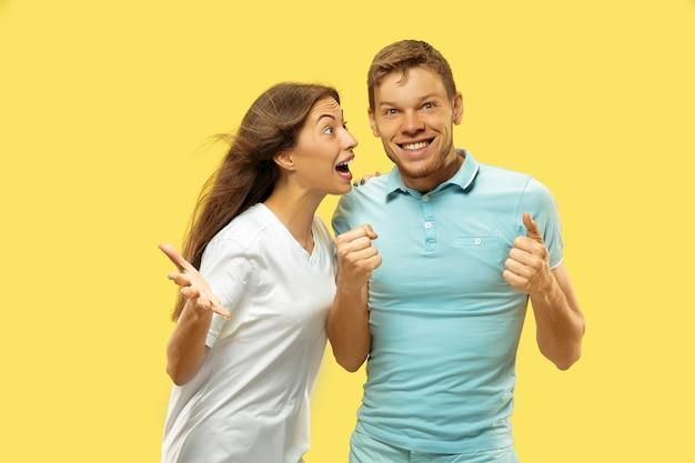 Halblanges porträt des schönen jungen paares. frau und mann in hemden feiern und zeigen das zeichen von ok. gesichtsausdruck, menschliches gefühlskonzept. trendige farben. Kostenlose Fotos
